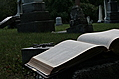 [picture: Open Bible and cross in graveyard]