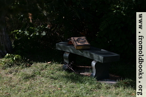 [Picture: Stone bench with books and cross]
